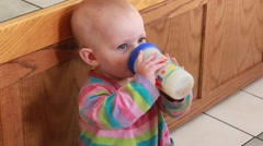 One year old takes big drink from her sippy cup Stock Footage