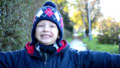 Portrait child - little boy smiles and jupms - autumn - nature and sidewalk Stock Footage