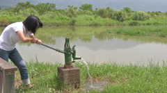 Hand-Powered Water Pump. People pump the old water hand pump - stock footage