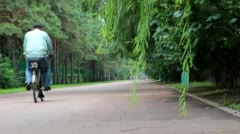 Riding bike on road in woods Stock Footage