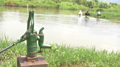 Hand-Powered Water Pump. People clearing the lake near a hand pump Stock Footage