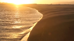 Sand blowing across beach at sunset Stock Footage
