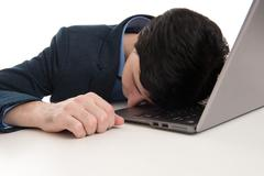 Stock Photo of overworked businessman sleeping on his laptop