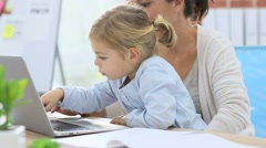 Little girl and working mom sing laptop computer Stock Footage