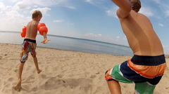 children running into the sea to swim - stock footage