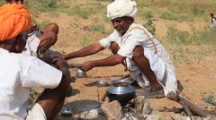 Indian man preparing food over a campfire in the desert. Rajasthan, India Stock Footage