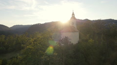 Aerial - Church on hill at sunset with surrounding of trees Stock Footage