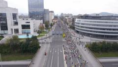 Aerial - People on city streets running marathon over the highway bridge Stock Footage