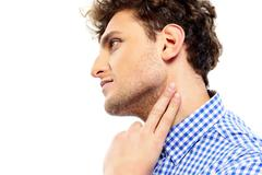 portrait of a man touching his neck - stock photo