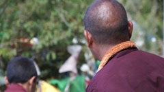 Spitting tibetan monk and lungta flags. Stock Footage