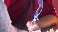 Tibetan doctor writing mantras Stock Footage