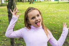 Cute girl with put out tongue Stock Photos