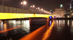 Orange illuminated London Bridge by night Stock Footage