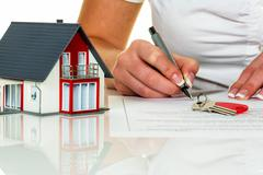 woman signs purchase agreement for house - stock photo
