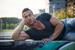 Handsome muscular blond man laying down in city Stock Photos