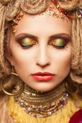young woman with fashion makeup and closed eyes on brown background - stock photo