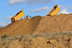 Dump truck unloading soil during road works - stock photo