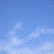 Rain drops on window pane and blue sky Kuvituskuvat