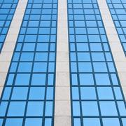 blue sky reflected in grid of windows - stock photo