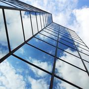 Reflecting clouds in glass facade Stock Photos