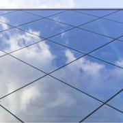 reflexions of clouds and blue sky in facade of modern building - stock photo