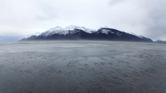 Dust storm over frozen Chilkat River with mountains behind Stock Footage
