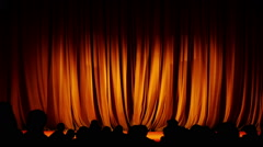 Closing orange curtain and silhouettes of people leaving the hall theater Stock Footage