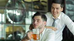 Two successful friends businessmen drink beer and rejoice and shout together - stock footage