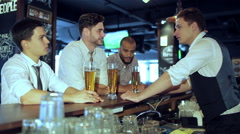 Three friends sitting at the bar and keep the beer - stock footage