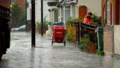 Postman delivering letters in heavy rain Stock Footage