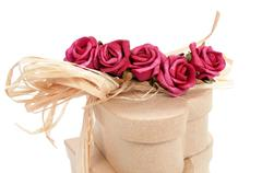 Stock Photo of heart-shaped gift boxes tied with natural raffia and topped with artificial r
