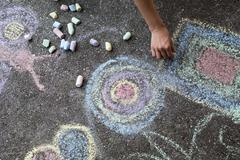 woman paints with colored chalk on asphalt - stock image - stock photo