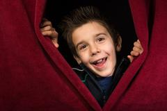 Child appearing beneath the curtain - stock photo