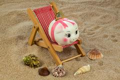 deck chair with piggy bank and euro - stock photo