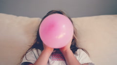 Girl inflating a pink balloon Stock Footage
