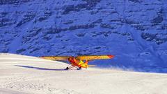 Landing of yellow airplane at the swiss winter mountain ski resort Stock Photos
