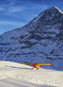 yellow red airplane landing at the mountain airfield in swiss alps - stock photo