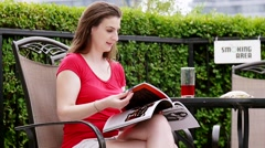Confident Woman reading a magazine on the pation Stock Footage