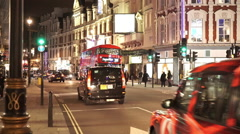 Red Bus driving through Shaftesbury Avenue in London Westend by night Stock Footage