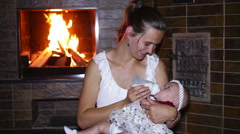 Mother feeds her baby with a bottle near a fireplace Stock Footage