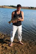 Fisherman with his big carp at a beautiful river. - stock photo