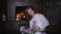beautiful girl sitting near the fireplace and watching photo album - stock footage