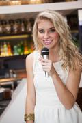 Blonde woman smiling while singing into a microphone - stock photo