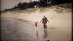 1301 - grandpa and granddaughter walk the shoreline - vintage film home movie - stock footage