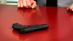 Man takes gun off of counter Stock Footage