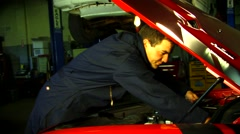 Man in auto garage working on hotrod Stock Footage