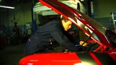 Man in garage working on hotrod Stock Footage
