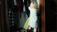 Young girl hangs up coat Stock Footage