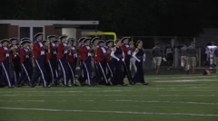 Band marches in step onto the field for halftime Stock Footage