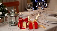 Christmas theme. Festive table setting with candles, gifts and Christmas lantern - stock footage